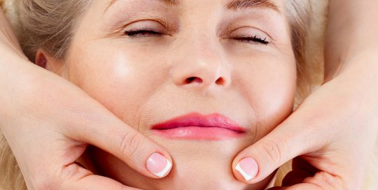 Eine blonde Frau liegt mit geschlossen Augen und Haende massieren ihr Kinn.