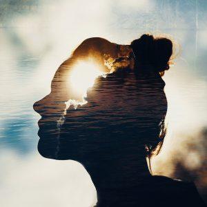 Eine Frau, die in die Sonne blickt. Man glaubt, das Licht aus ihrem Kopf strahlt.