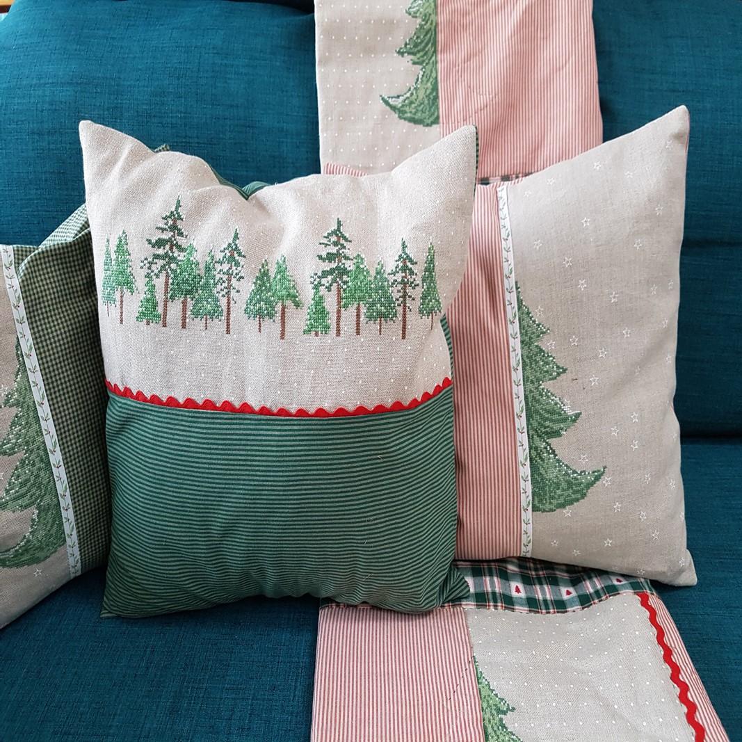 Angeordnete Weihnachtspolster auf einem tuerkisen Sofa. Die Polster sind mir Nadelbaeumen bestickt und in beige, natur und rot gehalten.