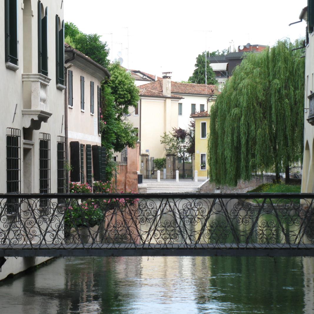Eine schmale Brücke, von Haus zu Haus über ein Flüsschen. Romantisch fließt es unter einem