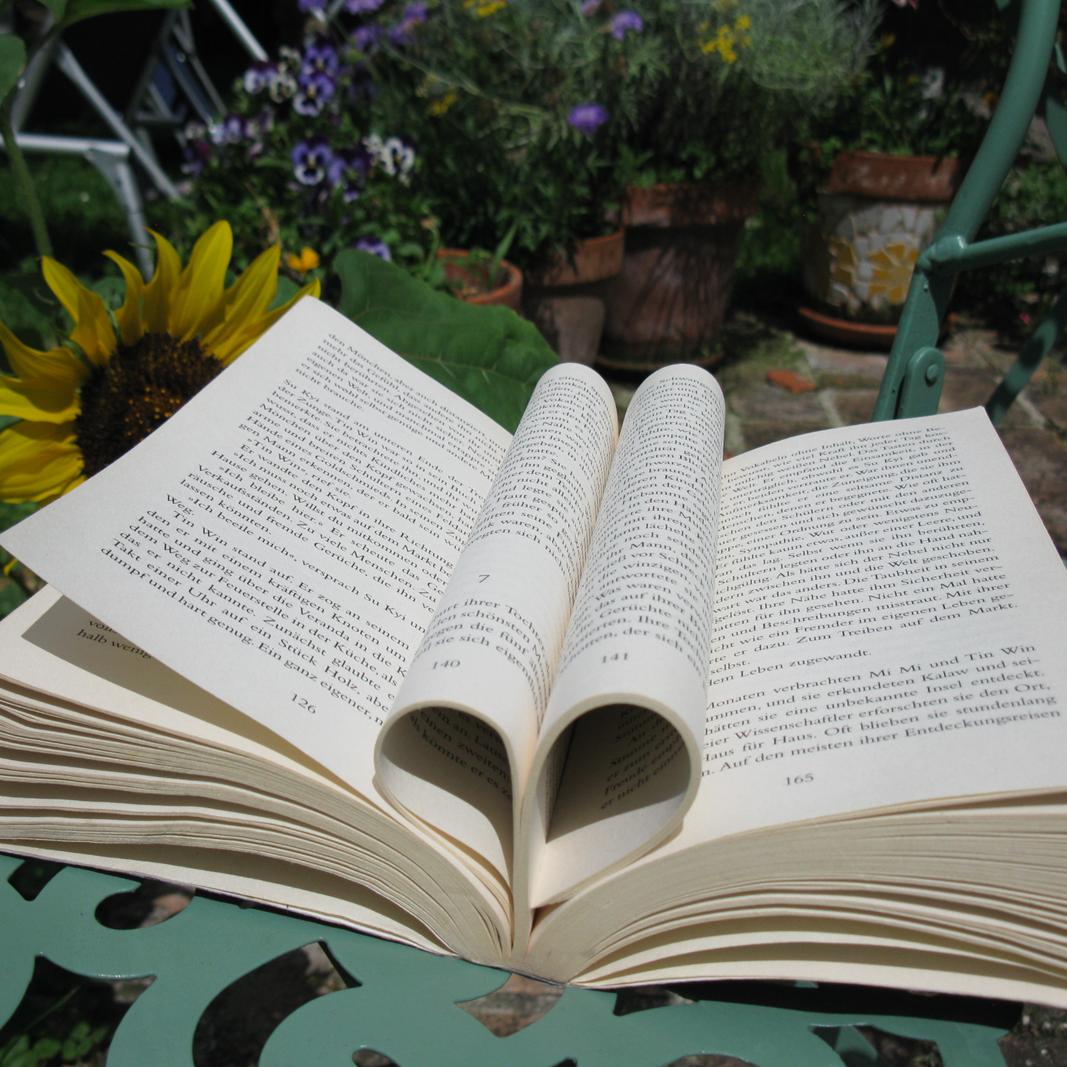 Ein offenes Buch mit einem Herz in der Mitte aus den zusammengeklappten Seiten.