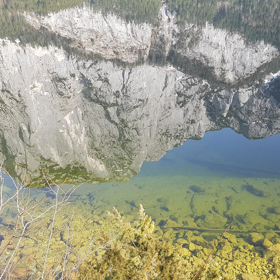 Ein Berg spiegelt sich im Wasser des glasklaren Sees
